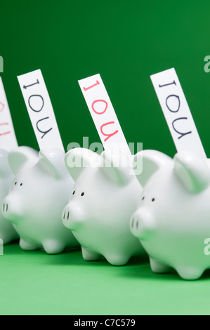 Group of piggy banks with IOU's coming out of coin slots - Stock Photo