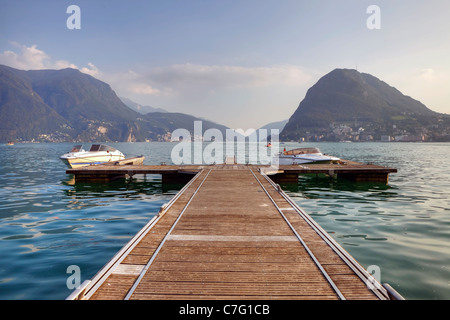 an impressive boat dock on Lake Lugano, with views of Monte Salvatore - Stock Photo
