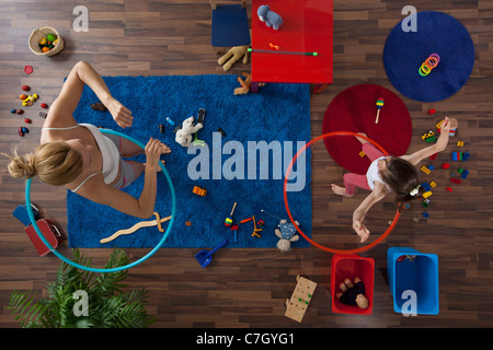 A mother and daughter using hula hoops in their living room, overhead view - Stock Photo