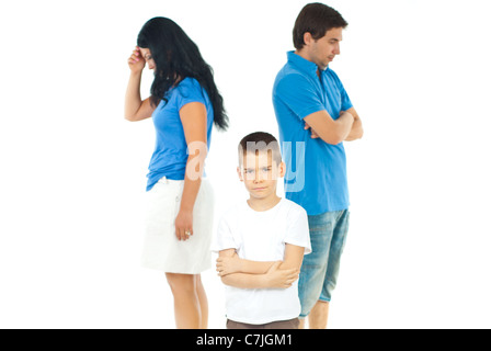 Upset boy standing with arms folded in front of parents with problems against white background - Stock Photo
