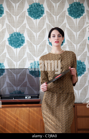 Woman in vintage dress with vinyl record - Stock Photo
