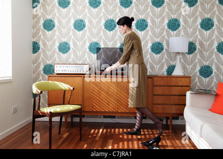 Woman in vintage dress playing records - Stock Photo