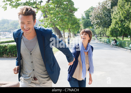 Couple walking with the Eiffel Tower in the background, Paris, Ile-de-France, France - Stock Photo