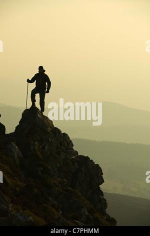 Man hiking on rocky hillside - Stock Photo