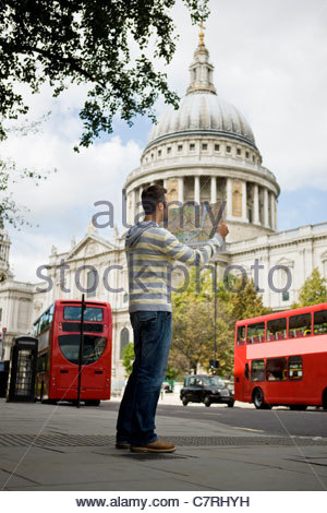 A mid-adult man standing in front of St Paul's cathedral, looking at a map - Stock Photo