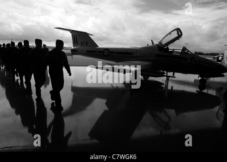 St. Thomas, Canada - June 25, 2011. Members of 'Snowbirds' are silhouetted as they march into a hanger at an Air - Stock Photo