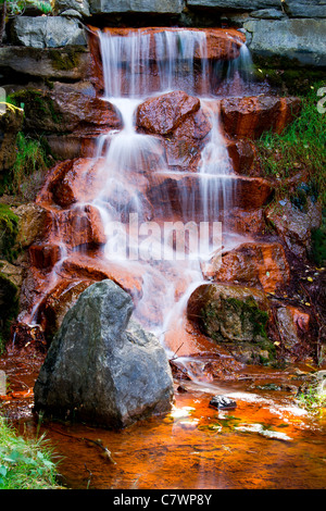 The cascading waters of a beautiful waterfall flow down over red algae covered stones in Andrew Haydon Park in Ottawa, - Stock Photo