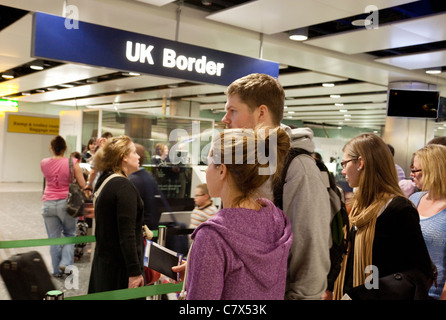 Young people waiting to enter the UK Border at immigration, Terminal 3, Heathrow airport, London - Stock Photo