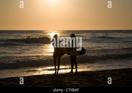 Surfer couple chatting on seashore against sunset in Laguna Beach - CA - Stock Photo