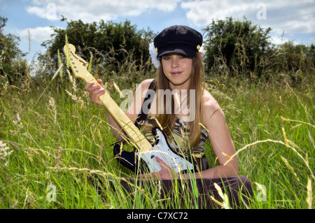 Attractive young caucasian woman with a hippy chick look playing with guitar in meadow in Bristol uk on summer day - Stock Photo