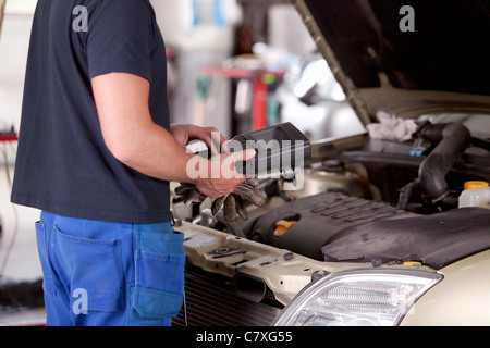 Detail of a mechanic using electrnoic diagnostic equipment to tune a car - Stock Photo