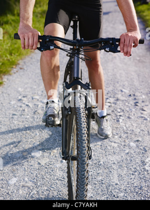 sports activity: young adult cyclist riding mountain bike in the countryside. Vertical shape, cropped view, low - Stock Photo