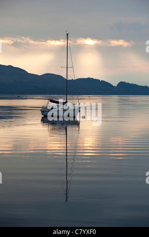 A sailing yacht moored in Loch Lomond, Scotland as the sun rises. - Stock Photo