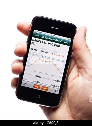 Using a live stock market trading app on a smartphone smart phone mobile phone - Stock Photo