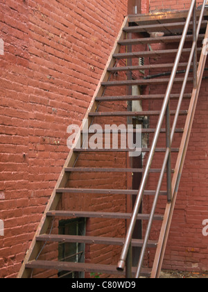 Iron fire escape up brick building - Stock Photo