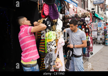London Camden Town Lock Stables market two Asian young men set up shop store stall of novelty animal hats pavement - Stock Photo
