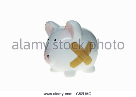 Close-up of adhesive bandages on a piggy bank - Stock Photo