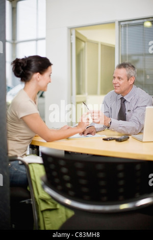Woman signing papers with car salesman - Stock Photo