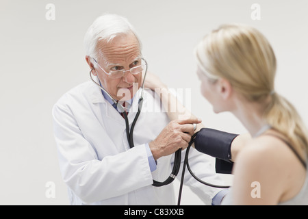 Doctor taking patient's blood pressure - Stock Photo
