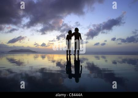 Children standing on beach at sunset - Stock Photo