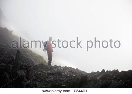 Silhouette of hiker on rocky hillside - Stock Photo