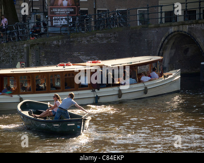 Boats on the water in the city centre of Amsterdam, the Netherlands - Stock Photo