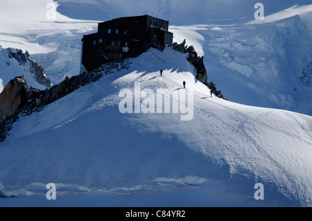 Alpinistes approaching the Cosmiques hut above Chamonix - Stock Photo
