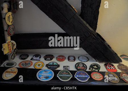 Pub interior of The Cherub Inn in Dartmouth showing traditional beer mats displayed on the wall. - Stock Photo