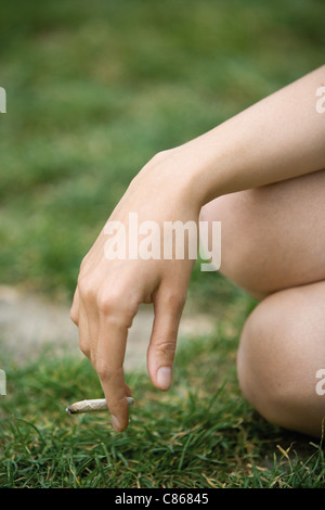 Woman holding a marijuana joint, cropped - Stock Photo