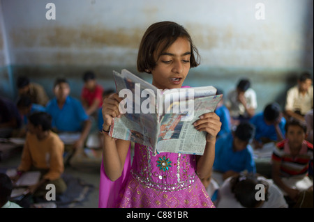 Indian girl reading aloud during English lesson at Rajyakaiya School in Narlai village, Rajasthan, Northern India - Stock Photo