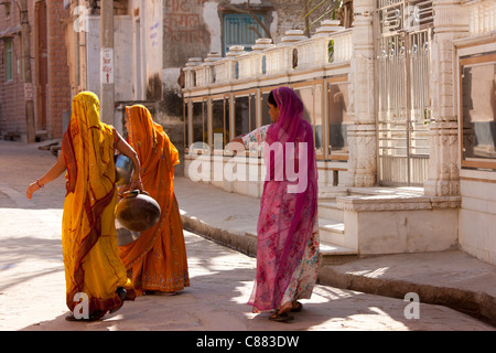 Rajasthani women carrying water pots in the village of Narlai in Rajasthan, Northern India - Stock Photo