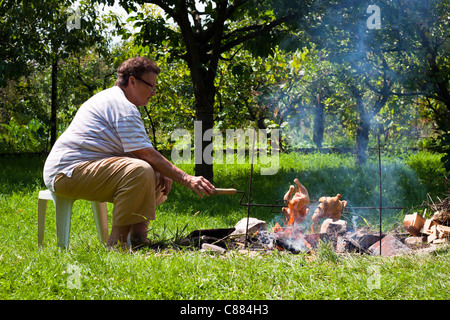 Senior woman grilling chickens on bonfire. - Stock Photo
