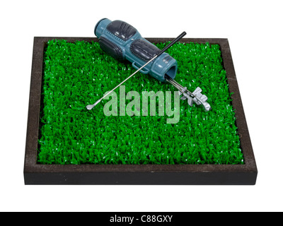 Golf bag used to carry the clubs and balls used during the game laying on green grass - path included - Stock Photo