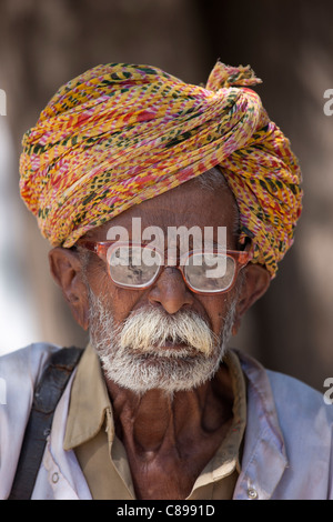Indian man, the local barber, in typical Rajasthani village of Nimaj, Rajasthan, Northern India - Stock Photo