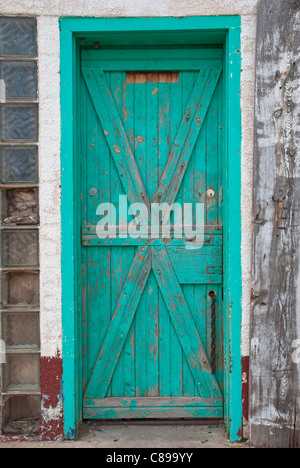 An old green door conceals unknown property in an abandoned building in Ft. Sumner, New Mexico. - Stock Photo
