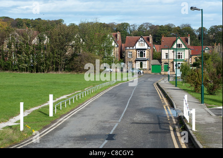 Metal road barrier across a tarmacked driveway to restrict traffic at certain times. - Stock Photo