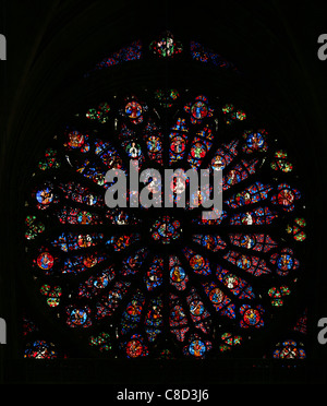 Central rose window with the medieval stained-glass window in the Notre-Dame Cathedral in Reims, France. - Stock Photo