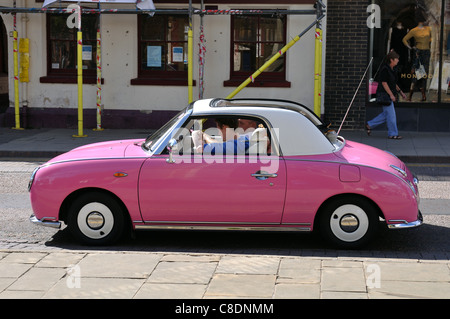 A pink Nissan Figaro car - Stock Photo