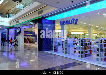 People in Boots pharmacy chemist beauty shop front & window in Westfield shopping centre mall in Stratford City - Stock Photo