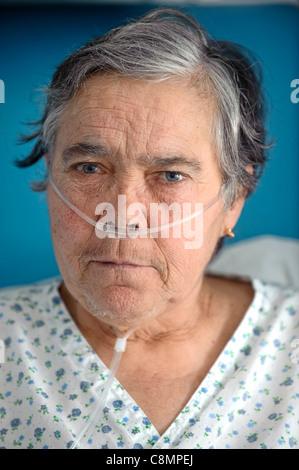 Portrait of elderly woman wearing oxygen nasal tube - Stock Photo
