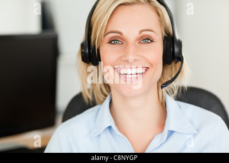 Close up of a blonde woman wearing headset looking into camera - Stock Photo