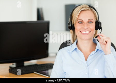Close up of a blonde smiling woman wearing headset looking into camera - Stock Photo