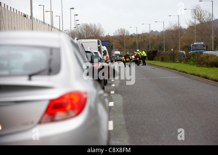 Police motorcycle officers clear debris from a road traffic accident in the outside lane of a dual carriageway in - Stock Photo