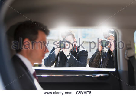 Paparazzi taking pictures of politician in car - Stock Photo
