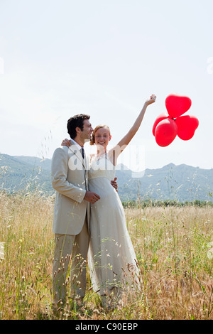 Newlyweds in field with red heart shape balloons - Stock Photo