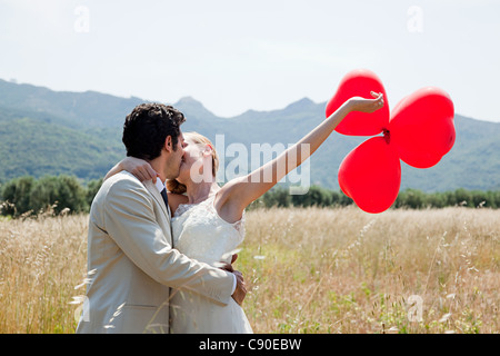 Newlyweds kissing in field with red heart shape balloons - Stock Photo