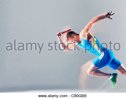 Blurred view of athlete running with baton - Stock Photo