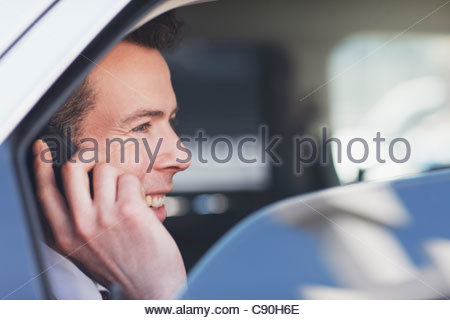 Politician talking on cell phone in backseat - Stock Photo