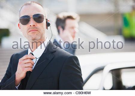 Bodyguard talking into earpiece - Stock Photo