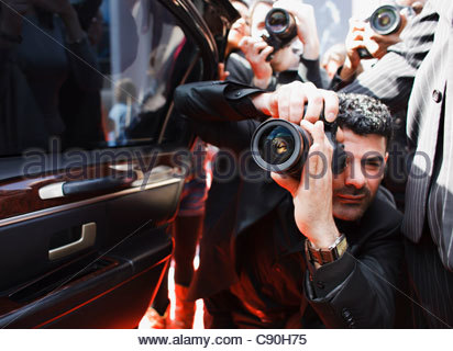 Paparazzi taking pictures of celebrity in car - Stock Photo